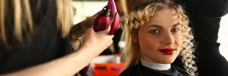 Young Woman Getting Curly Hair by Curling Iron. Styling Wavy Hairstyle for Beautiful Client. Girl Sitting with Funny Long Lock. Hairstylist Making Hairdo in Beauty Salon Looking at Camera Shot