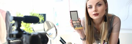 Stylish Blogger Recording Beauty Blog Tutorial. Blogging, Ecommerce Concept. Beautiful Female Makeup Artist Holding Shadow Palette while Recording Product Review for Vlog. Bunch of Brushes in Tube