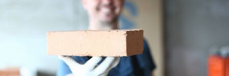 Focus on male hand presenting concrete block. Happy smiling constructor man in protective outfit holding red brick in one hand and looking at camera with gladness. Building concept