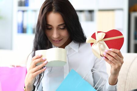 Portrait of joyful businesswoman sitting in modern office and holding heartshaped box. Lovely brunette looking at gift with tenderness. Shopping concept. Blurred background