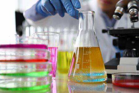 Chemistry industry lubricant oil test concept. Female chemist in blue protective gloves hand hold test tube with yellow liquid. Make analysing sample petroleum gasoline fuel in chemical laboratory.