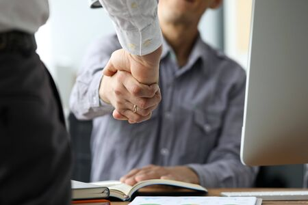 Two male clerks shaking hands at workplace close-up. Symbol of beginning of new positive promising relationship for future opportunities concept