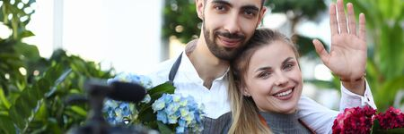 Happy Vlogger Holding Domestic Flowers in Pot. Man and Woman Florist Recording Video for Plant Vlog. People Showing Blue and Red Hydrangea in Flowerpot to Camera. Gardener Looking at Camera Shot