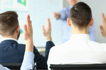 Focus on woman holding raised handing up to express opinion. Responsible employees inquiry questions to speaker and discussing business plan. Company meeting concept