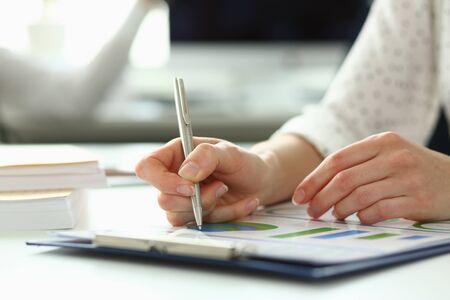 Nahaufnahme von zarten weiblichen Armen, die etwas in einen Papierordner mit einem wichtigen Vertrag schreiben, der das Einkommen des Unternehmensgewinns stark erhöhen kann. Firmenmeeting-Konzept