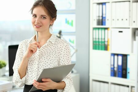 Portrait of personable smiling woman in meeting room. Businesswoman posing in modern office and looking at camera with gladness. Company concept. Blurred background
