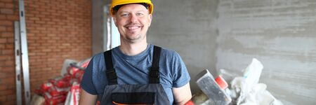 Portrait of smiling man holding big red hammer and wearing yellow hardhat and construction gloves. Laughing constructor looking at camera joyfully. Building concept