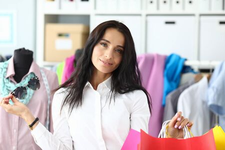 Portrait of smiling woman standing in fashionable clothes store and holding multicolored packets with brand new outfits. Gorgeous lady looking at camera with calmness and happiness. Shopping concept Stock Photo