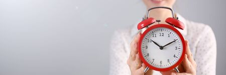 Focus on red alarm clock. Beautiful model in white blouse with curly brunette hair indicating on time. Copy space in left side. Isolated on grey background