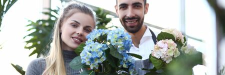 Man and Woman Florist Holding Hortensia Flower. Blonde Girl Holding Blue Hydrangea in Flowerpot. Smiling Male Gardener Showing White Blooming Plant with Green Leaves Looking at Camera Shot