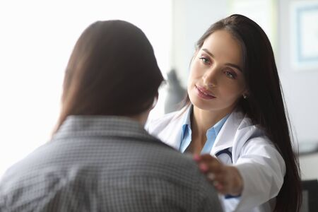 Portrait of doctor looking at patient with calmness. Upset visitor sitting in clinic cabinet. Cute therapist calming worrying ill female. Healthcare and treatment concept Stock Photo