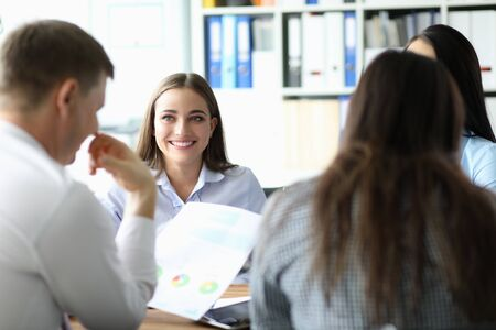 Portrait of business team discussing new profitable project with colleagues. Cheerful businesslady speaking about annual report and statistics data. Business meeting and teamwork concept