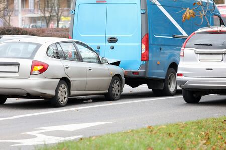 Auto crash on road. Accident of two vehicles in motion. Damaged automobile with broken bumper. Van and small transport at street of city. Breakdown of autocar in town Stock Photo