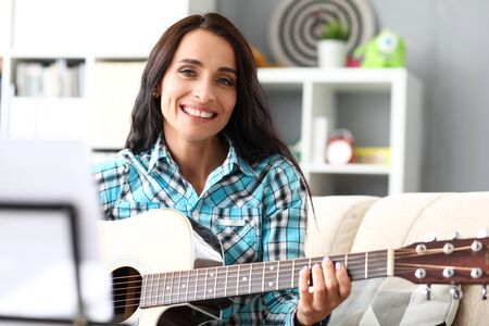 Portrait of attractive woman with charming smile. Musician in casual shirt sitting on comfortable sofa and playing stringed musical instrument. Music and art concept
