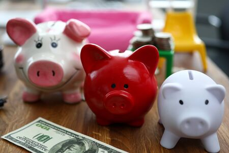 Focus on multicolored stashing pigs standing on wooden table with green banknotes and miniature plastic furniture on background. Funding capital and investment concept Stock Photo