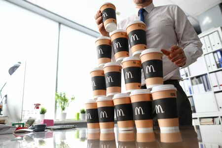 Minsk, Belarus - September 26, 2019: Male clerk building big tower out of mcdonalds cardboard cups