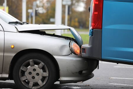 Focus on damaged bumper of vehicle in car accident in city. Damaged parts of transport. Automobile with breakdown and crashed details. Collision of auto on road Stock Photo