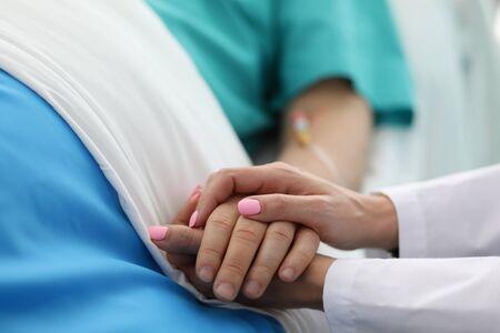 Close-up van mensen die elkaars hand vasthouden. Vrouw kalmerend voor zieke patiënt in ziekenhuisafdeling. Doc vraagt naar het welzijn van de zieke. Gezondheidszorg en geneeskunde concept