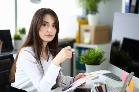 Portrait of smiling woman thinking about best color for styling. Wonderful businesslady choosing color scheme. Business and art designing concept. Blurred background