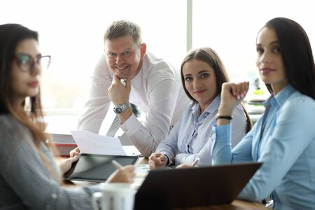 Portrait of cheerful businesswoman and businessman discussing annual report. Perfect woman and man looking at camera with gladness. Business company and teamwork concept