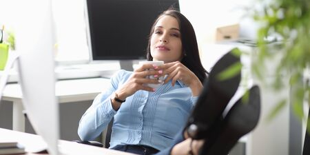 Portrait of smiling beautiful businesslady resting from hard work. Attractive businesswoman drinking coffee on workplace in comfortable office. Business concept