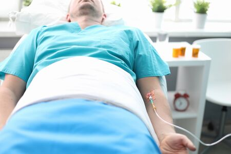 Focus on person lying in hospital bed with intravenous injection for recovery. Patient of medical center with catheter in vein. Treatment of sickness and diseases