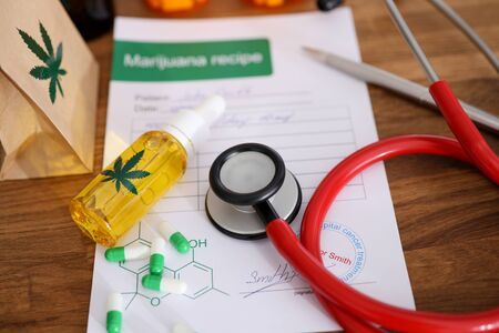 John Smith - fictitious name. Red stethoscope with marijuana recipe on doctor table background closeup. Herbal cancer treatment concept Banco de Imagens
