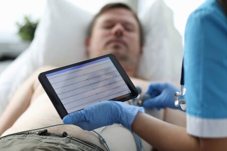 Focus on doctor hands in medical gloves touching screen of modern tablet examining condition of patient illness with heart diagrams. Healthcare and clinic concept