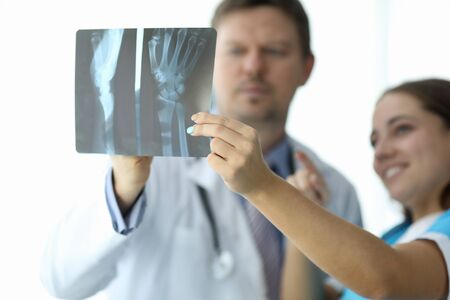 Focus on refined female hand of cute woman holding snapshot. Professional hakeem and nurse making diagnosis to patient. Medicine and healthcare concept Imagens - 134964142