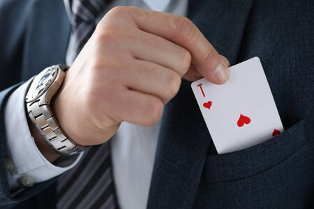 Male businessman hand hold playing card in hand against casino background closeup. Custom solutions in business concept