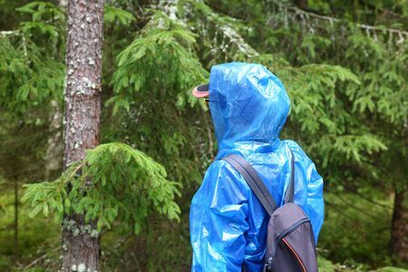 Woman in blue protective polyethylene raincoat agains forest background. Search for get missing people concept