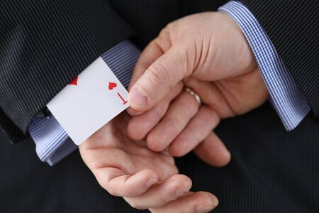Close-up of cheater hands pulling ace card out of sleeve with crossed arms behind. Gamer with strong addiction to games. Bribe casino and dishonesty concept Stockfoto