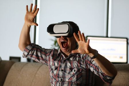 Man sits at home on the couch uses virtual reality glasses rides on a roller coaster screaming in fear. Software tester concept Reklamní fotografie
