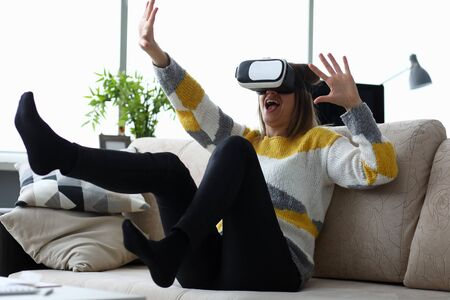 Woman sits at home on the couch uses virtual reality glasses rides on a roller coaster screaming in fear. Software tester concept 版權商用圖片