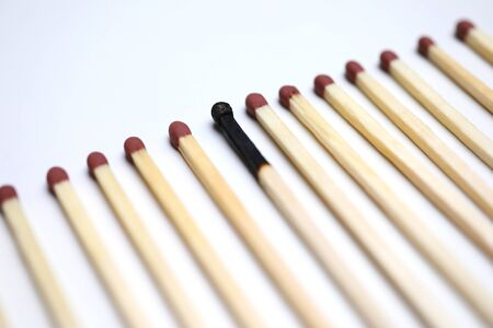 One burnt match among many new whole close-up background. Wrong hr manager head hunter choice concept