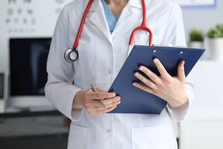 Close-up of female doctor wearing white uniform, stethoscope and holding paper folder with medical prescriptions in hospital. Medicine and healthcare concept Stock Photo
