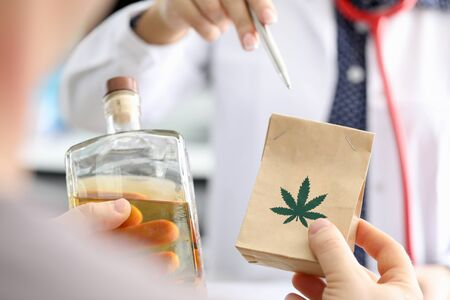 Close-up view of doctor prescribing marijuana to patient. Package with cannabis and bottle with liquid. Drug as treatment. Medicine and alternative folk therapy concept