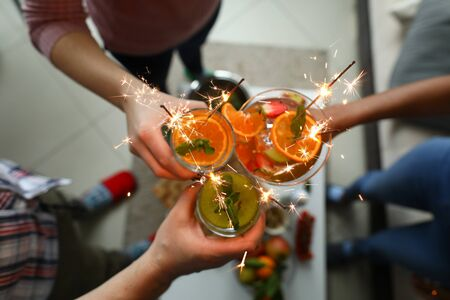 Young group friends hold in hand fruit cocktail with sparkler decoration. Christmas invite party concept. Heath care vegan summer drinks 版權商用圖片