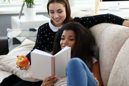Two woman friend read book sit on coach against house background portrait. LGBT Movement same sex relationships concept. female hand hold apple health vegan food lifestyle