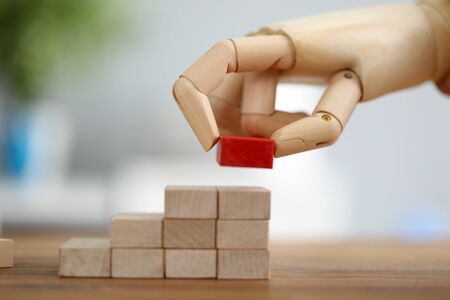 Close-up view of mechanical hand putting red block on stack of wooden bricks. Building success foundation. Business growth process and uniqueness concept