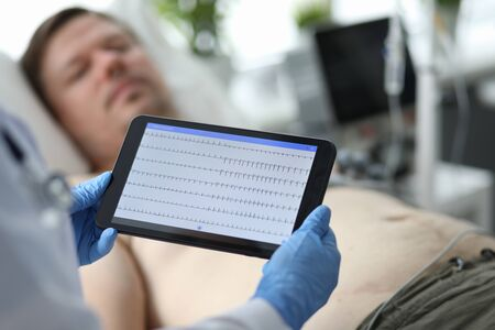 Focus on hands of female doctor examining condition of patient illness heart and touching screen of modern tablet with cardiogram. Medicine and healthcare concept Imagens