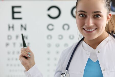 Portrait of smart practitioner standing in clinic office and performing eyesight check to patient pointing to letters. Doctor wearing white medical gown and stethoscope. Vision test concept