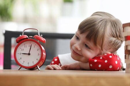 Portrait of smiling girl sitting at table and playing with alarm-clock. Cheerful little kid looking at alarm with gladness and interest. Concept of childhood