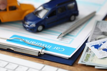 Close-up of important papers about car assurance. Credit bank card and currency money lying on table. Blue and orange toy cars on folder. Advertisement and business concept
