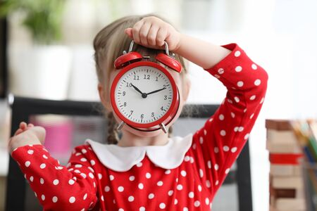 Joyous girl covering face with red alarm-clock. Little child wearing cute polka-dot dress and playing at children room. Baby toying with alarm. Concept of childhood
