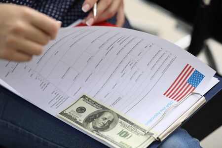 Close-up view of female carefully reading usa visa application form before complete. Cash money stick to clipboard. Embassy fee. Legally entry to country concept