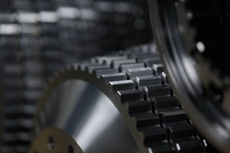 Close-up of metallic cogs nested in modern factories for rapid and transit production of diverse kinds of details. Automotive manufacturing process concept
