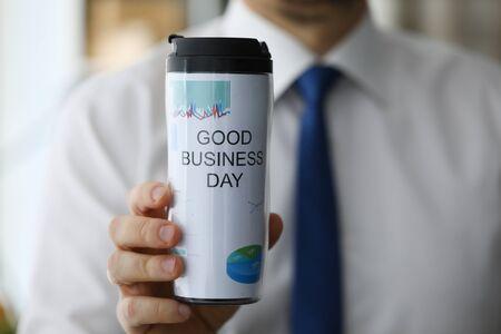Mann hält in der Hand Thermoflasche mit Heißgetränk Nahaufnahme. Guter Geschäftstag mit Kaffeegetränk-Konzept Standard-Bild