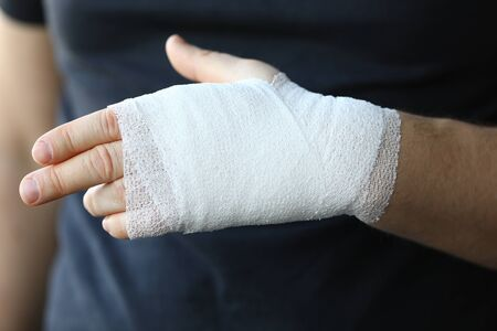 Male hand with tight elastic bandage on arm closeup. Self help sprain concept