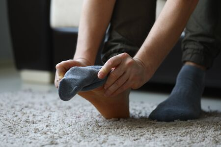 Man at home in morning puts gray socks on his leg. For a long time do not change clothes concept